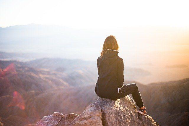 Kvinna sittandes på toppen av ett berg