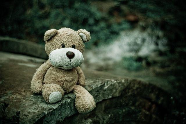 Ledsen teddybjörn sittandes på en sten